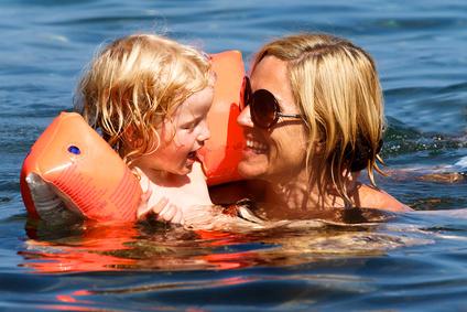 Mutter und Kind mit Schwümmflügeln im Meer