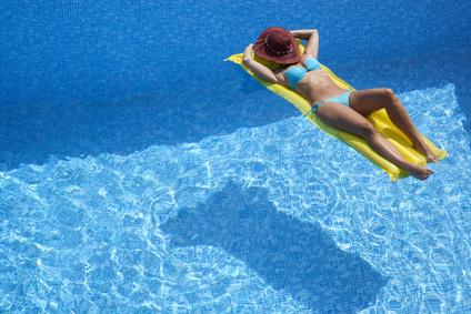 Frau mit Hut entspannt auf Luftmatratze im Pool