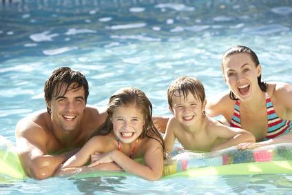 Junge Familie, die auf Luftmatratze im Pool relaxt