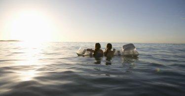 Zwei Mädchen mit Luftmatratze schwimmen in Richtung Horizont