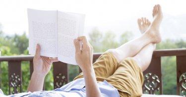 Junger Mann, der auf Balkon auf selbstaufblasbarer Luftmatratze relaxt und liest