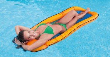 Junge Frau die auf einer orangenen Intex Lounge Mesh Luftmatratze entspannt auf dem Wasser liegt