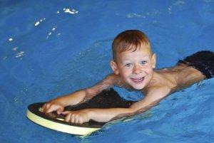 Junge schwimmt in Schwimmbad mit Schwimmbrett und hat Spaß